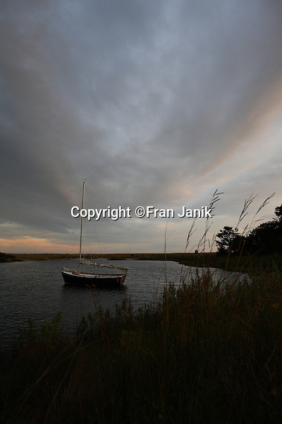 A single sailboat sits at rest in cove under dramatic clouds at sunset on the Island of Martha's Vineyard. The Island is located off the coast of Massachusetts, to the south of Cape Cod. Settled by the English in 1642, it became an important center of fishing and whailing during the 18th and 19th centuries.