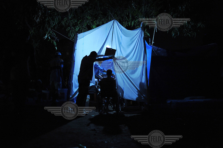 A man pushes a child in a wheelchair into a makeshift clinic in a dark park in the city centre. The clinic is run by medical students with the little medecine they could gather. Thousands of people have made shelter in the city's parks eleven days after an earthquake hit the country. .A 7.0 magnitude earthquake struck Haiti on 12/01/2010. Early reports indicated that more than 100,000 may have been killed and three million affected.