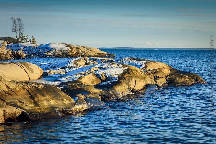 Vinter klippor med lite snö vid havet på Gålö i Stockholms skärgård