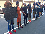 """On Tuesday July 12, 2016 Black Lives Matter sympathetic protestors stood silently with their hands up outside Skylight Clarkson Square, the main venue for the men's fashion shows. They wore t-shirts that read """"Stop Killing Us"""" and """"Walter Scott"""", to protest the killing of unarmed African-Americans by police in various cities across the United States. The protest was organized by Hannah Stoudemier who stated, """"I work for Lanvin, and when I walked into work they didn't have anything to say about it. But they were on their phones watching while Aston Sterling got shot. I have a black brother, nephew. I have a daughter, and so I do this today so she wouldn't have to do this when she gets older."""""""