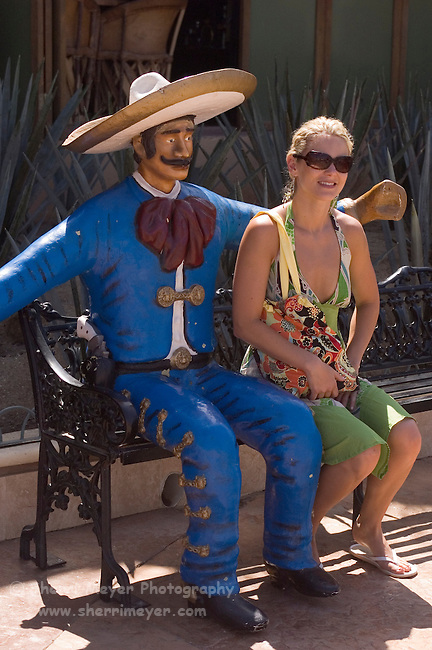 Tourist sitting with a statue of a Mexican Cowboy (Vaquero) at the Marina, Cabo San Lucas, Baja California, Mexico