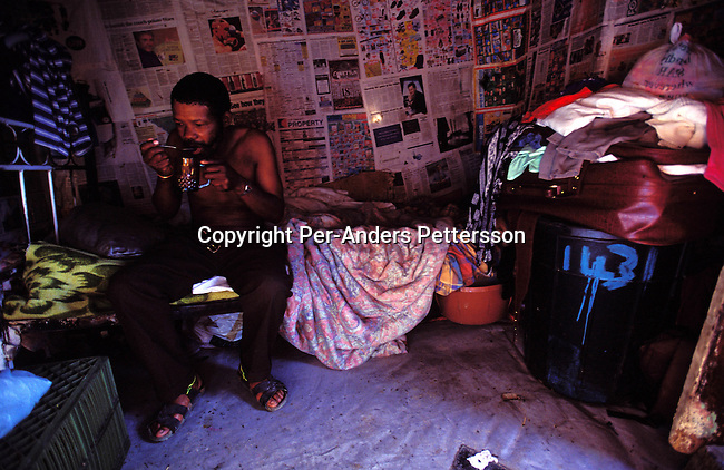 ditown00215 .Digital.Township  An unidentified man having tea in his house for breakfast on June 25, 2001 in Site B Khayelitsha, a township about 35 kilometers outside Cape Town, South Africa. He is one of many that come to Cape Town from rural areas to look fro work. Khayelitsha is one of the poorest and fastest growing townships in South Africa. People usually come from the rural areas in Eastern Cape province to find work as maids and laborers. Most people don't find work and the unemployment rate is very high, together with lot of violence and a growing HIV-Aids epidemic itÕs a harsh area to live in..©Per-Anders Pettersson/iAfrika Photos.