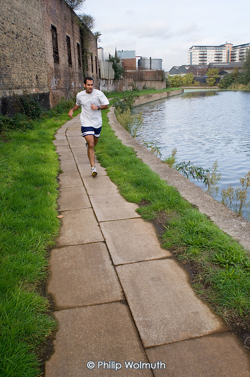 A jogger on the towpath by the Lea Navigation in the Lower Lea Valley, site of the 2012 Olympic Games.