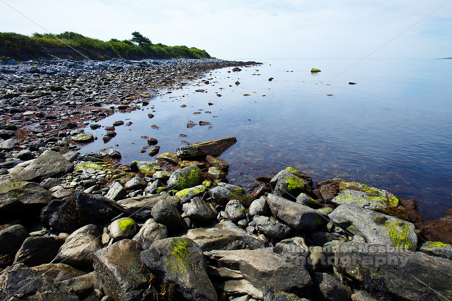 Middletown, RI - The rocky shore of Sachuest point curves out from Second (Sachuest) beach on a dead calm summer morning