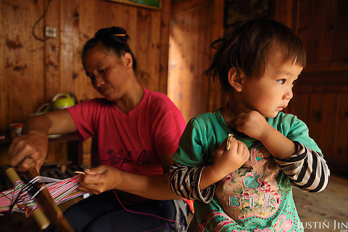 A woman weaves a ribbon for her two-year-old granddaughter.