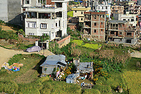 NEPAL Kathmandu, city growth, loss of agricultural fields, a remaining tin-shed hut and paddy fields / Staedtewachstum, Verlust von landwirtschaftlicher Flaeche, letzte Huette und Reisfelder