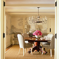 The dining room is dominated by a round Charles X mahogany table and a 19th century Italian bed crown made into a chandelier