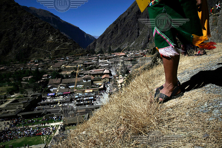 A woman stands above the town of  Ollantaytambo during the annual re-enactment of the battle of the same name. The battle occurred in January 1537 when an army under Spanish conquistador Hernando Pizarro were held by the Incan forces of the emperor Manco Inca.
