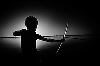 "A small indian boy plays with his arrow and bow at the margins of Araguaia river, one of the major rivers of Brazil, and the principal tributary of the Tocantins, Amazon rainforest. Roughly in the middle of its course, the Araguaia splits into two forks (with the western one retaining the name Araguaia and the eastern one being called Rio Javaés). These later reunite, forming the Ilha do Bananal, the world's largest river island. The mouth of the Javaés forms a broad inland delta where it pours back into the main Araguaia, a 100,000 hectare expanse of igapó flooded forest, blackwater river channels, and oxbow lakes called Cantão. This is one of the biologically richest areas of the eastern Amazon, with over 700 species of birds, nearly 300 species of fish (more than in all of Europe), and large populations of threatened species such as the giant otter, the black cayman, and the world's largest freshwater fish, the pirarucú, all occurring within a relatively small area. ""Araguaia"" means ""River of the Macaws"" in the native Tupi language."