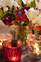 A vase of red roses dusted with snow and white freesias forms part of a Christmas table decoration