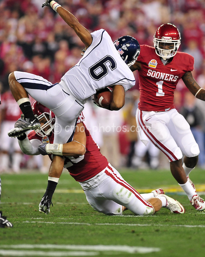 Jan 1, 2011; Glendale, AZ, USA; Connecticut Huskies wide receiver Kashif Moore (6) gets tackled by Oklahoma Sooners linebacker Travis Lewis (28) in the 2nd quarter of the 2011 Fiesta Bowl at University of Phoenix Stadium.