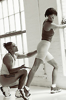 Personal training session: man assists and gives advice to woman about her stretching.