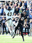 SIOUX FALLS, SD, NOVEMBER 26:  Luke Papillion #15 from the University of Sioux Falls passes the ball around the leaping Benjamin Shields #43 from Harding University Saturday afternoon at Bob Young Field in Sioux Falls. (Photo by Dave Eggen/Inertia)