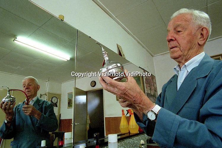 .Foto: VidiPhoto..ARNHEM - De oudste kapper van Nederland, de 91-jarige Herman van Eijk uit Arnhem, stopt er mee. Na 76 jaar kapper te zijn geweest, vindt hij het nu welletjes. Volgende maand gaat hij met pensioen. Hij begon op vijftienjarige leeftijd in Breda. Knippen kostte toen nog een kwartje. Herman heeft z'n zaak alleen 's morgens open. Hij knipt heren, geen dames. Die zijn nooit tevreden, vindt hij. De zaak van Van Eijk staat nog vol met oude kapperspullen.