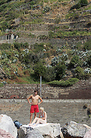 Bagnanti sugli scogli a Vernazza, uno dei borghi delle Cinque Terre, sormontata dai vigneti.<br /> Bathers on the rocks in village of Vernazza at the Cinque Terre.<br /> UPDATE IMAGES PRESS/Riccardo De Luca