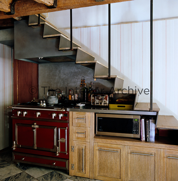 The cooker in the basement kitchen is cleverly tucked under the staircase with the extractor and units following the line of the steps