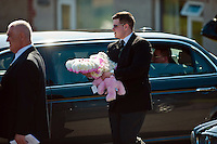 Tuesday 11 March 2014<br /> Pictured: A pink wreath and a toy are carried by a man from the service<br /> Re: A funeral has taken place  in Pontyberem Catholic Church for six day old Eliza-Mae Mullane who died after an incident at the family home in Carmarthenshire in the morning of 18 February 2014, where police later seized two dogs, an Alaskan Malamute called Nisha and a collie cross that were destroyed following the baby girl's death.<br /> Parents Sharon John and Patrick Mullane said previously that they would cherish the short time they had with her.