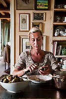 Chef Maddalena Caruso sitting in her country kitchen carefully peeling the skin off fresh figs in preparation for poaching