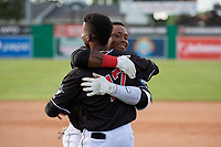 Batavia Muckdogs Albert Guaimaro (13) hugs Dalvy Rosario (17) after a walk off single during a NY-Penn League game against the Auburn Doubledays on June 19, 2019 at Dwyer Stadium in Batavia, New York.  Batavia defeated Auburn 5-4 in eleven innings in the completion of a game originally started on June 15th that was postponed due to inclement weather.  (Mike Janes/Four Seam Images)