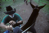 "Eldon ""Buzzy"" Sproat helps me secure my saddle as we prepare to descend to the leper colony on the Kalaupapa peninsula in 1995. Sproat helped create the Kalaupapa mule tours on Molokai. He passed away on June 14, 2014 at age 76."