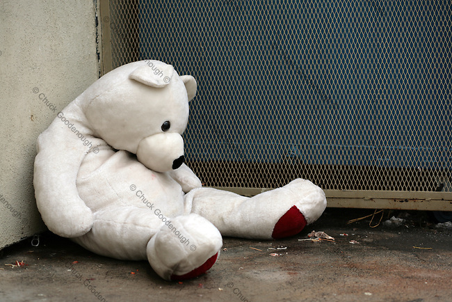 Stock Photo of a Teddy Bear Stuffed Animal Sitting with Head Down Near Alley Dumpster