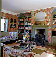 The cosy wallpapered sitting room has built-in bookcases either side of the fireplace