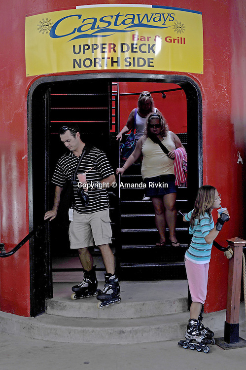 Rollerbladers stand by the entrance to the rooftop bar and restaurant Castaways at the North Avenue beach in Chicago, Illinois on August 18, 2008.