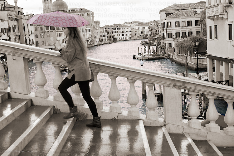 A female figure walks over a large bridge in Venice holding an umbrella