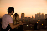 A couple watches the sunset over the downtown Los Angeles skyline