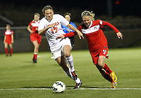 BOYDS, MARYLAND - April 06, 2013:  Ingrid Wells (9) of The Washington Spirit pushes past Kaili Torres (17)  of the University of Virginia women's soccer team in a NWSL (National Women's Soccer League) pre season exhibition game at Maryland Soccerplex in Boyds, Maryland on April 06. Virginia won 6-3.