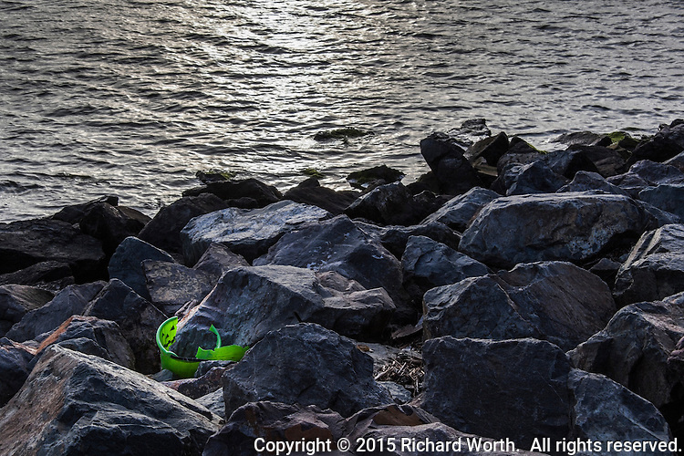 The tattered remains of a child's green plastic bucket lie among the rocks along the San Francisco Bay shoreline at the San Leandro Marina Park.