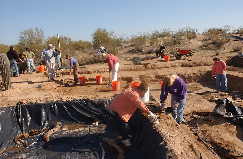 Wannasarn Noonsuk, a University of Hawaii, (foreground orange shirt) and Tanya Wang a.University of arizona .student shovels dirt to be screened of dirt from.the Marana Platform mound looking for.shards and other artifacts from the .mound occupied for 100 years by the HoHoKam.people from 1200 ad to 1300 ad.....in this picture the students are evacuating.a room 40x40 in size, they have divided it up into.four sections and are working one quarter at a time...