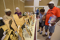 NWA Democrat-Gazette/BEN GOFF @NWABENGOFF<br /> Jonathan Scott and wife Linda Scott (right) look at carvings by cousin Wilson Scott of the Bella Vista Woodcarvers Club, with wife Amy Scott, all of Bella Vista, Saturday, July 15, 2017, during the Bella Vista Woodcarvers Club's Artistry in Wood Show at Bella Vista Assembly of God church. Members of the club exhibited and sold their woodwork at the show, which also included door prizes, demonstrations and a people's choice award.