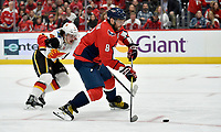 WASHINGTON, DC - NOVEMBER 03: Capitals left wing Alexander Alex Ovechkin (8) takes a shot on net while Flames defenseman Rasmus Andersson (4) sticks checks him during the Calgary Flames vs. Washington Capitals on November 3, 2019 at Capital One Arena in Washington, D.C.. (Photo by Randy Litzinger/Icon Sportswire)