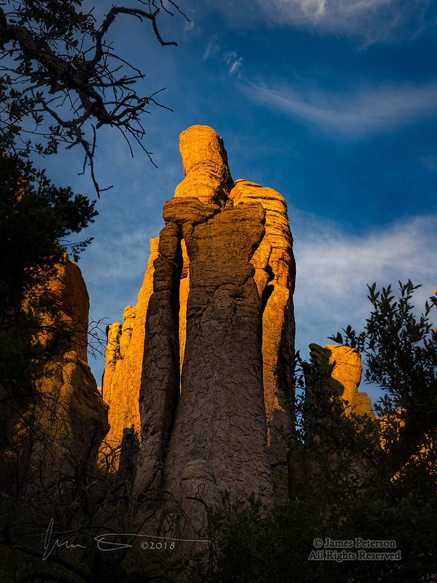 Needle Arch, Chiricahua National Monument, Arizona ©2018 James D Peterson.  Looming over the Hailstone Trail, this tall but narrow rhyolite arch is easiest to spot just before sunset, when it stands out against the glowing monolith behind it.