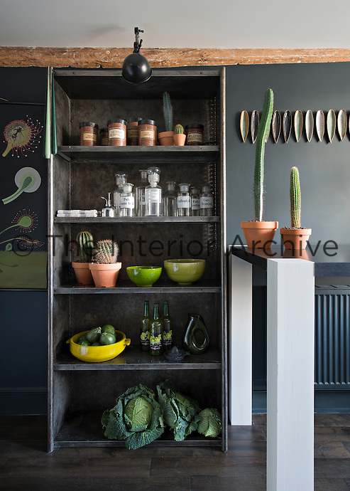 In the kitchen-diner, a bold colour approach of black and shades of grey is offset with items in varying shades of green. A breakfast bar is situated to one side of the room providing a dining space. Storage jars and tableware are neatly arranged on a pair of free-standing metal shelving units.