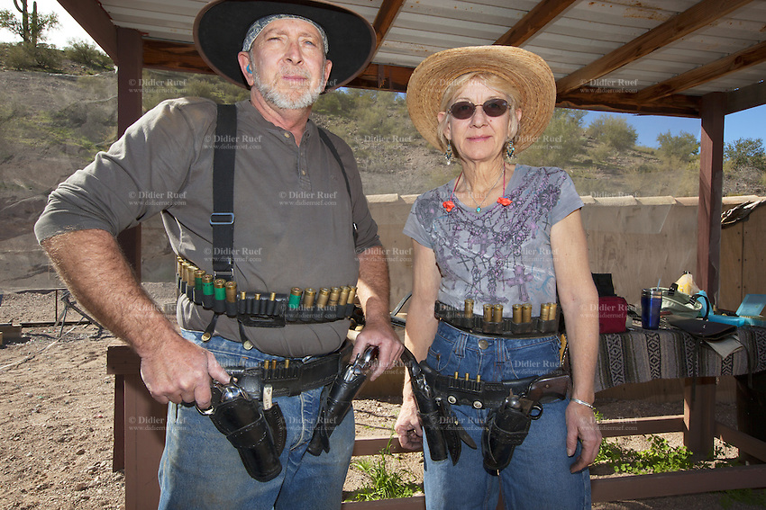 USA. Arizona state. Peoria. Peoria is distant 50 km from Phoenix. Cowtown Cowboy Shooters Association. Fake town scenery from the old Far West time. Jeff and Gail are a couple, dressed with cowboys outfits, which trains outdoors for the incoming Winter Range - SASS National Championship of Cowboy Action Shooting ( february 22nd-28th, 2016). Gail is the manager of the <br /> Cowtown Shooting Range. The Single Action Shooting Society (SASS) is a Cowboy Action Shooting (CAS, also known as Western Action Shooting, Single Action Shooting, or Cowboy 3-Gun). CAS is a type of multi-gun match utilizing a combination of pistol(s), rifle ( Winchester), and/or shotgun in a variety of &quot;old west themed&quot; courses of fire for time and accuracy. Participants must dress in appropriate theme or era &quot;costume&quot; as well as use gear and accessories as mandated by the respective sanctioning group rules. A CAS shooter engages a target with his lever-action rifle. Cowtown Shooting Range is a semi-private outdoor shooting range and firearms training facility. A firearm is a portable gun, being a barreled weapon that launches one or more projectiles often driven by the action of an explosive force. Most modern firearms have rifled barrels to impart spin to the projectile for improved flight stability. The word firearms usually is used in a sense restricted to small arms (weapons that can be carried by a single person). The right to keep and bear arms is a fundamental right protected in the United States by the Second Amendment of the Bill of Rights in the Constitution of the United States of America and in the state constitutions of Arizona and 43 other states. 31.01.16 &copy; 2016 Didier Ruef
