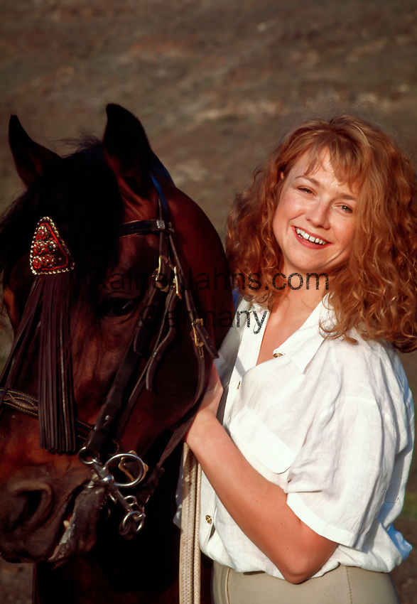 Spanien, Kanarische Inseln, Fuerteventura, junge Frau, rothaarig, mit Pferd, laechelt in Kamera | Spain, Canary Island, Fuerteventura, young woman, redheaded, with horse, smiling
