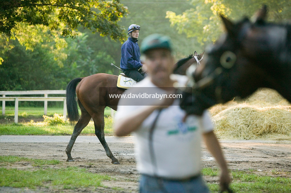 French jockey Julien Leparoux (L, background) rides back to the barn from an early morning breeze, or moderate speed workout ride, at Saratoga Springs, NY, United States, 5 August 2006.<br />