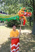 Dance team member holds head of ceremonial dragon with pole. Dragon Festival Lake Phalen Park St Paul Minnesota USA