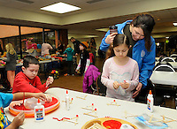 STAFF PHOTO FLIP PUTTHOFF <br /> SHEEP DOG CHRISTMAS GIFTS<br />  Carrie Sawyer, right, helps her daughter, Rebecca Sawyer, and her son, Gabe Sawyer, make crafts during the Sheep Dog Impact Assistance Christmas program on Saturday Dec. 20 2014 at the Center for Nonprofits in Rogers. Members of Sheep Dog Impact Assistance help families of military, law enforcement and fire service members who need assistance during the holidays and through the year, said Shain Scott with Sheep Dog. The event featured lunch, craft making and Christmas gifts for children.