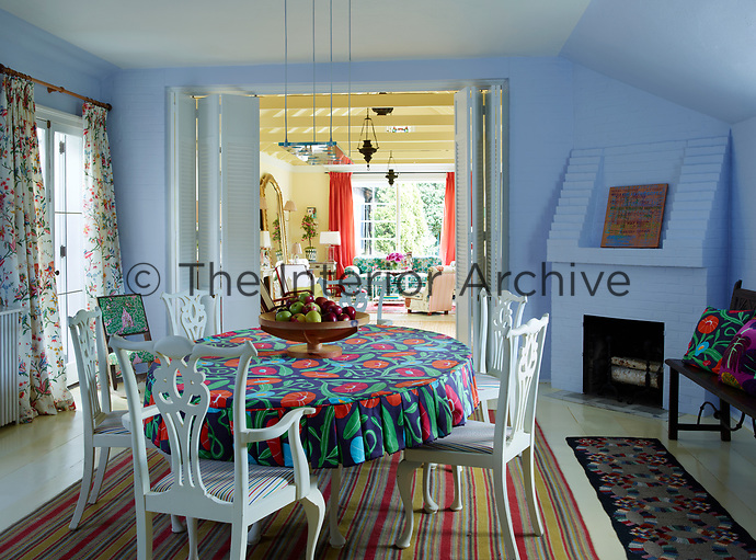 A white table and chairs stands on a striped rug in the centre of the blue dining room. A brick fireplace is built in to one corner. A pair of double doors leads through to the sitting room beyond.