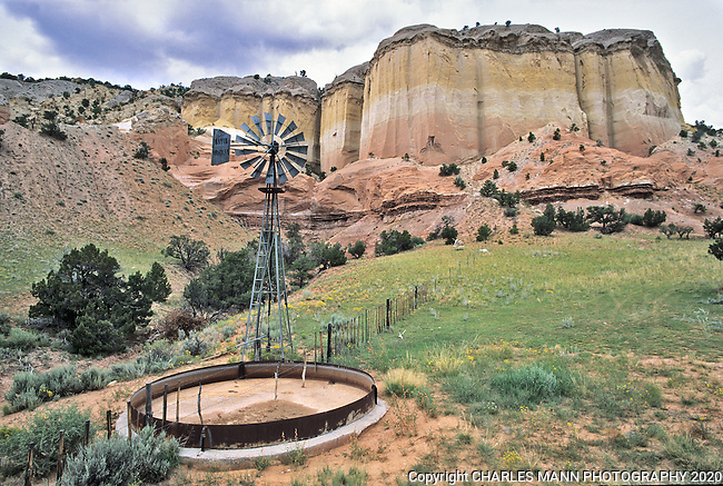 A windmill and water tank located at the base of a colorful sandstone cliff near Ghost Ranch in northern New Mexico preserve the feeling of the cattle culture in the western US.