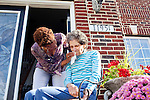 "Karen Morris has been caring for her mother Gloria, 80, for the past 10 years. Her mother has Alzheimer's disease and lives with Karen and Karen's husband Richard in their Charlotte, NC home. She wipes her mother's face as the pair sit on the front porch in the sun...Mrs. Morris was a nurse before she retired and really enjoys taking care of people, she said. Every morning she washes her mother in the bathroom, helps her walk down the stairs, and they share breakfast, as they did Monday, October 18, 2010...Gloria was having an especially bad day and because Karen sees her every day, she knew something was wrong. She later discovered her medication was dehydrating her. That is one of many reasons why having a regular caretaker is so important. ..Released: Yes.""Caretaker"".Assignment c/o Ilene Bellovin"