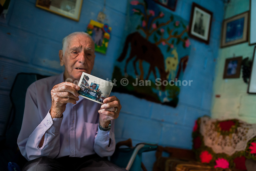 """Francisco Flores, one of the first inhabitants of the Pablo Escobar neighborhood, shows a picture taken at Pablo Escobar's funeral, in Medellín, Colombia, 6 December 2017. Twenty five years after Pablo Escobar's death, the legacy of the Medellín Cartel leader is alive and flourishing. Although many Colombians who lived through the decades of drug wars, assassinations, kidnappings, reject Pablo Escobar's cult and his celebrity status, there is a significant number of Colombians who admire him, worshipping the questionable """"Robin Hood"""" image he had. Moreover, in the recent years, the popular """"Narcos"""" TV series has inspired thousands of tourists to visit Medellín, creating a booming business for many but causing a controversial rise of narco-tourism."""