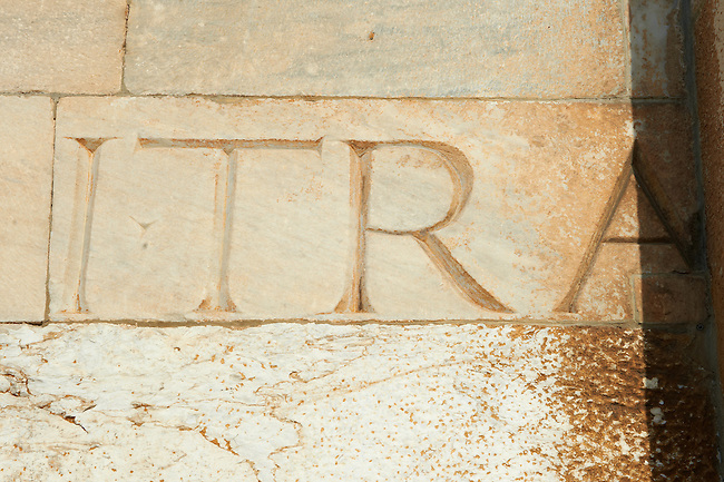 Roman lettering in the reused masonary from an earlier Roman temple in the exterior of the Duomo Pisa, Italy