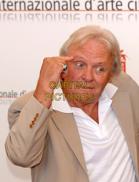 "SIR ANTHONY HOPKINS.Photocall for ""Cinderella Man"".La Biennale, Venezia.62nd Venice Film Festival, Italy.5 September 2005.Ref: PL.half length beige suit jacket finger to head gesture funny wide eyes.www.capitalpictures.com.sales@capitalpictures.com.©Capital Pictures."