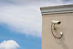 Building corner, sky,  and security camera.