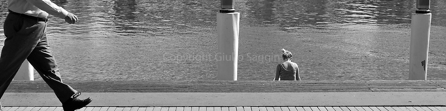 A woman sits by the water as a man strides past at Darling Harbour in inner Sydney.