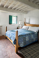 A guest bedroom has a rustic simplicity. Traditional local materials were kept during the restoration of the house, such as the terracotta tiles on the floor and ceilings and the original massive wooden beams, which have been painted white.